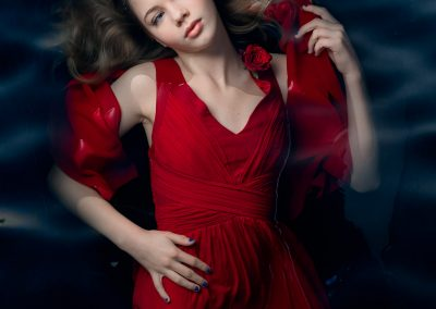 artwork by photorapher Ane Cathrine Buck my concotions lady in red dress floating in water